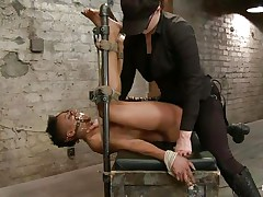 With her feet tied up and metal clamps all over her body the ebon slut endures a harsh punishment. This mistress knows what he's doing and gives her both pain and pleasure. This babe can't even scream as her mouth is folded with scotch tape. Look at that shaved pussy and how deep she's rubbing it with the vibrator.