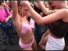 Chicks dance undressed in a big crowd outdoors
